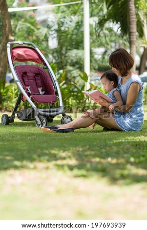 Chinese woman reading a book to her daughter while sitting in the park - stock photo