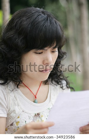 Chinese woman reading a sheet of paper