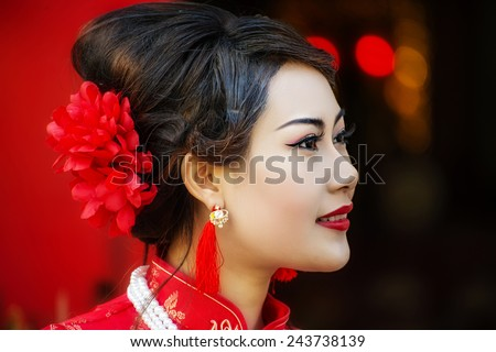 Chinese woman red dress traditional cheongsam ,close up portrait with red wood door - stock photo
