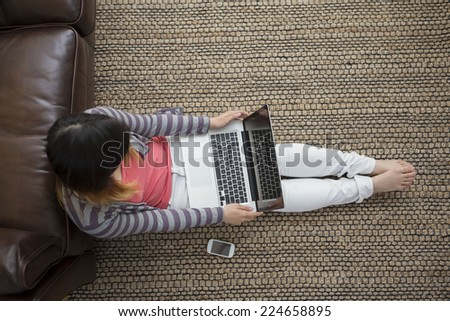 Chinese woman sitting on the floor at home and working with a laptop. View from above. - stock photo