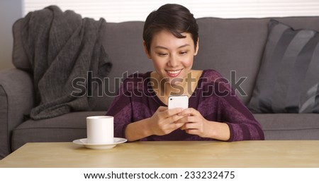 Chinese woman texting on phone by coffee table - stock photo