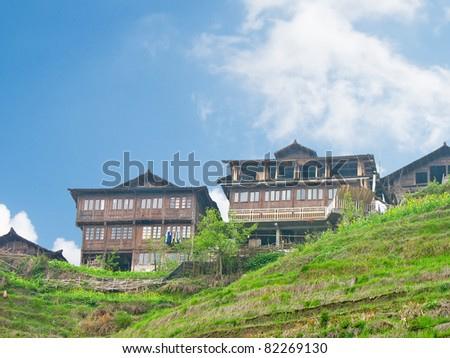 Chinese wooden buildings beside rice terrace, at Longji, Guilin, Guangxi Province, China