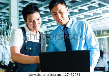 Chinese Worker or production manager and owner, ceo or controller, look on a laptop in a textile factory - stock photo
