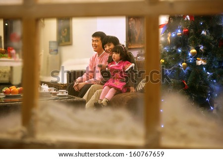 Chinese young couple with their daughter watching TV - stock photo