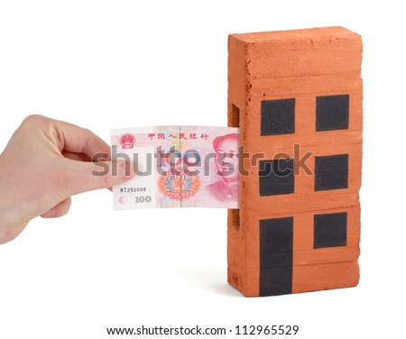 Chinese Yuan bank note being inserted to or drawn from a block of flats - stock photo