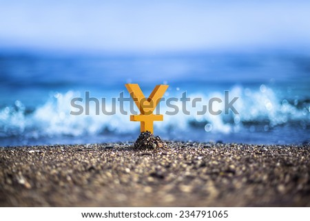 Chinese Yuan currency icon is standing on the wavy sea side - stock photo