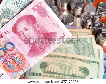 Chinese Yuan note in front of US Dollar notes - stock photo