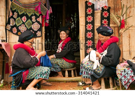 CHING RAI,THAILAND-AUGUST 30,2015 : Senior Mein or Yao Hill Tribe working embroidery of traditional clothes show for tourist in Akha Swing Festival, Doi Mae Salong, Chiang Rai in Northern of Thailand.