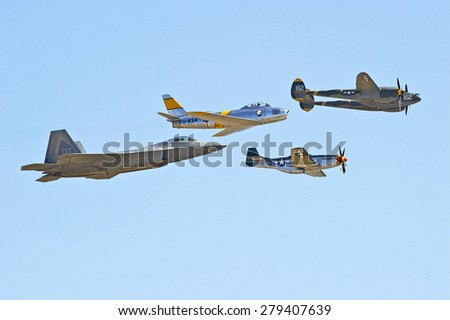 CHINO/CALIFORNIA - MAY 3, 2015: Lockheed Martin F-22 Raptor stealth tactical fighter and vintage WW II planes fly in formation at the Planes of Fame Airshow in Chino, California USA