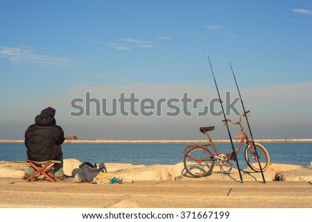 CHIOGGIA, ITALY - JANUARY, 01: Fisher man with fishing rods and bike on January 01, 2016 - stock photo
