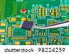 Chip in tweezers against the printed circuit board - stock photo