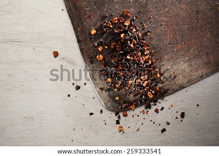 chipotle - jalapeno smoked chili flakes,   and whole in iron weight bowl on old textured metal - stock photo