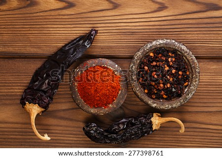 chipotle - jalapeno smoked chili flakes, milled  and whole in iron weight bowl on old textured wood - stock photo