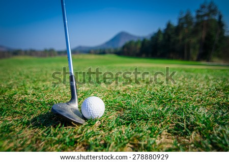 chipping a golf ball onto the green with driver golf club. Green grass with forrest and mountains in the background. Soft focus or shallow depth of field. Side view - stock photo