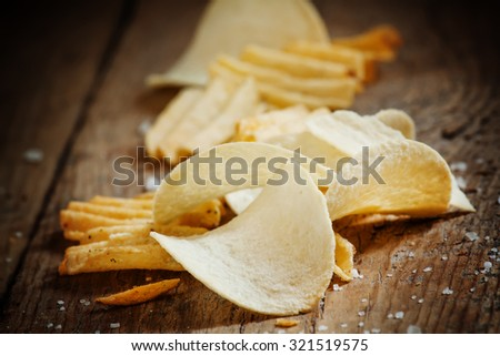 Chips and salt on old wooden table, selective focus - stock photo
