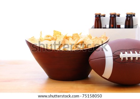Chips, football and Six Pack of Beer on a table with a white background. Horizontal format. Great for Bowl Game projects. - stock photo