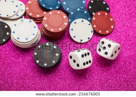 Chips for poker and dice on magenta background - stock photo
