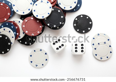 Chips for poker and dice on white background - stock photo