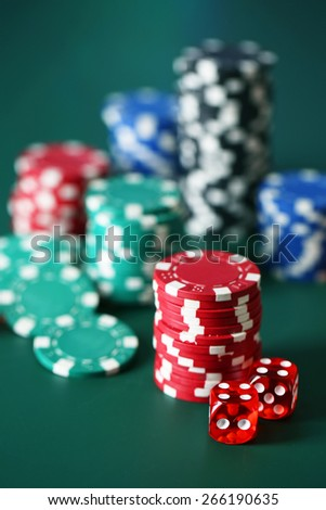 Chips for poker on green table - stock photo