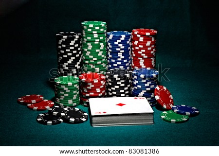 chips for poker with pile of cards - stock photo