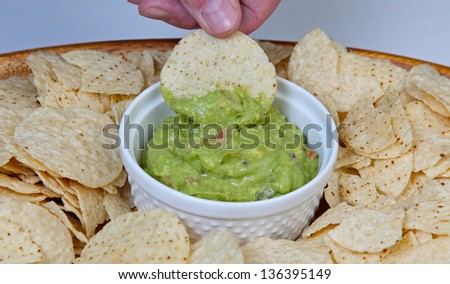 Chips & Guacamole against in a wooden serving platter against pale background - stock photo