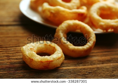 Chips rings on plate on wooden background - stock photo