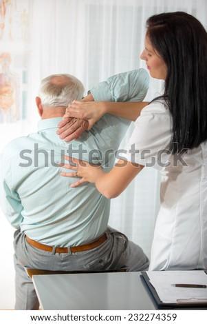 Chiropractic: Chiropractor examining senior man at office - stock photo