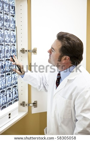 Chiropractic doctor examining a CT scan of the spine. - stock photo