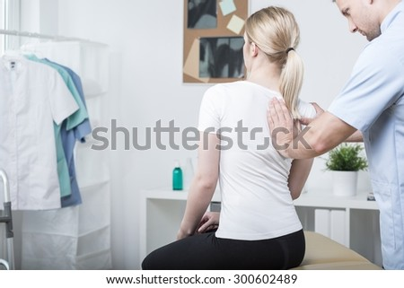 Chiropractic doing spinal mobilisation in physiotherapist's office - stock photo