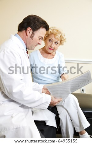 Chiropractor and his patient reviewing her medical history together. - stock photo