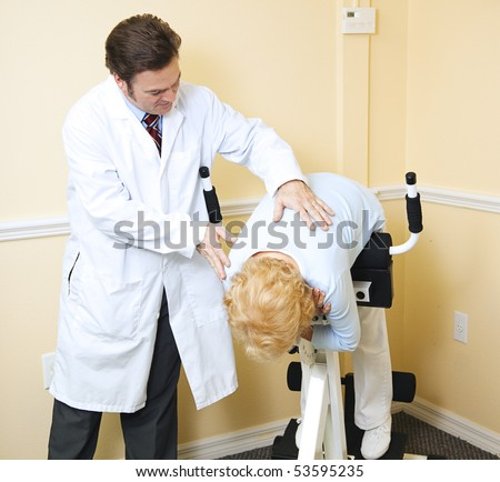 Chiropractor assists an elderly patient recovering from a back injury. - stock photo