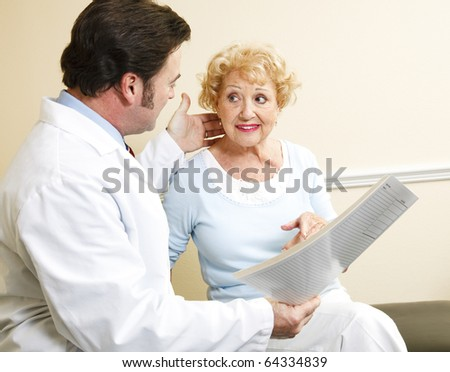 Chiropractor/doctor discussing treatment options with a beautiful senior patient. - stock photo