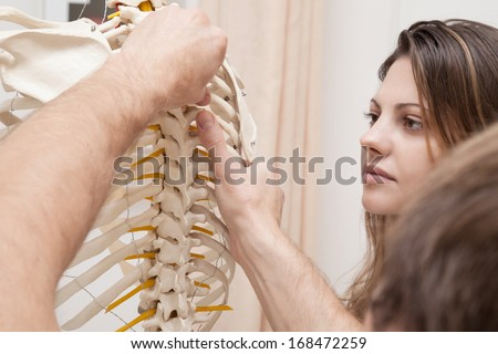 Chiropractor explains Patient using plastic model - stock photo