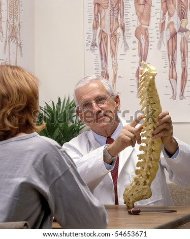 chiropractor showing a spine model to a patient - stock photo