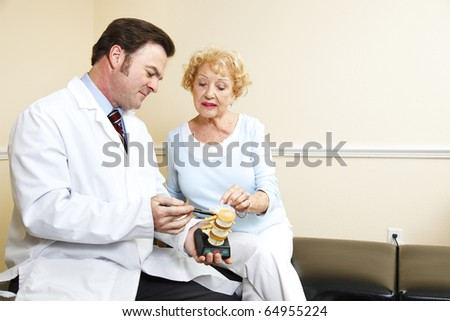 Chiropractor using a plastic model to explain treatment to his patient. - stock photo