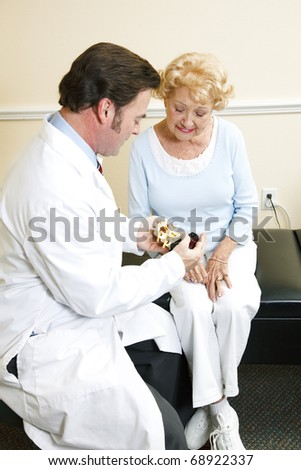 Chiropractor with a senior patient, looking at a model of the human spine. - stock photo