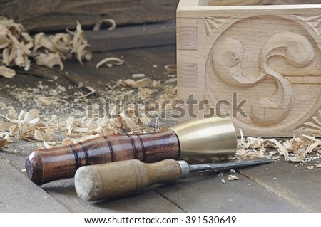 Chisel and hammer near beautiful wooden box with decor on floor - stock photo