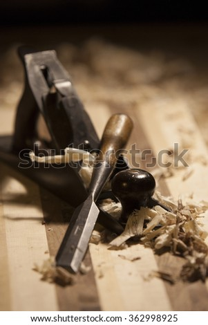 Chisel resting against a plane. Old fashioned wood-working tools. - stock photo