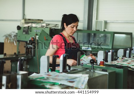 CHISINAU, MOLDOVA - APRIL 26, 2016: Workers in printing house. People working on printing machine in print factory. Industrial workers in Chisinau, Moldova on April 26, 2016