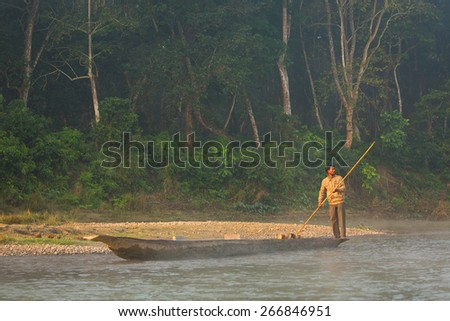 CHITWAN, NEPAL - NOVEMBER 23, 2014: Local man traveling by rowboat at wild river in Chitwan National Park Nepal.Park was established in 1973 and granted the status of a World Heritage Site in 1984.