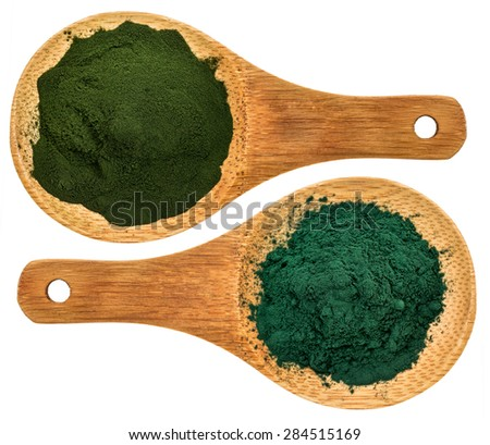 chlorella ans spirulina supplemt powder - top view of isolated wooden spoons - stock photo