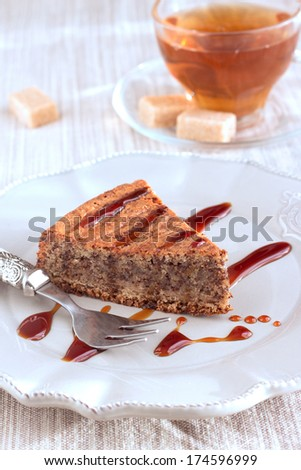 Chocolate and almond cake with caramel sauce, fork and sweet tea in transparent cup. On vintage brown plate and on natural pastel napkin with sugar pieces. Vertical.