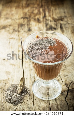 chocolate and banana milk smoothie with chia seeds on a dark wooden background in vintage high faceted glass. With a spoon of chia seeds. Concept of healthy food. selective Focus - stock photo