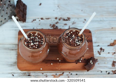 chocolate and banana smoothie with chocolate balls in jars  on white rustic table - stock photo