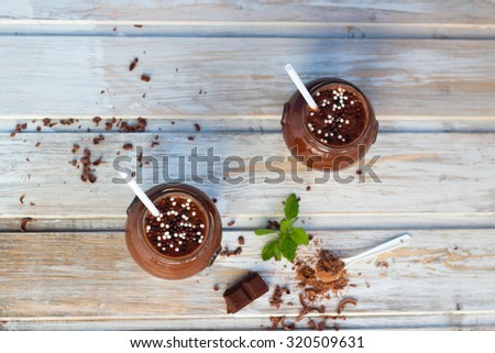 chocolate and banana smoothie with chocolate balls in jars  on white rustic table top view - stock photo