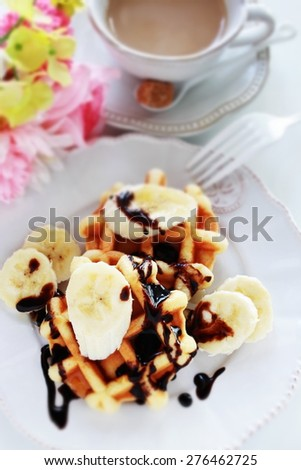 Chocolate and banana waffle with milk tea on background - stock photo