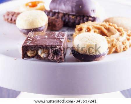 Chocolate and biscuits over white stand, horizontal image - stock photo