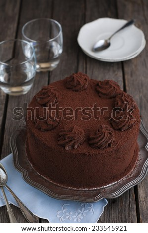 Chocolate and cocoa cake on old wood table - stock photo