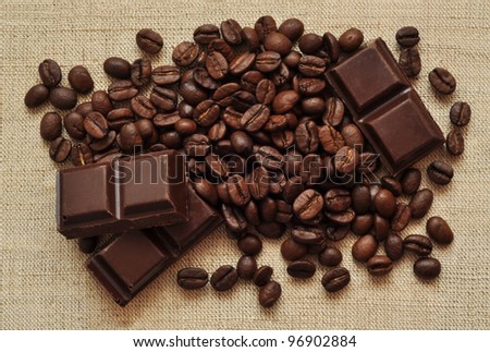 Chocolate and coffee beans on a textile background - stock photo