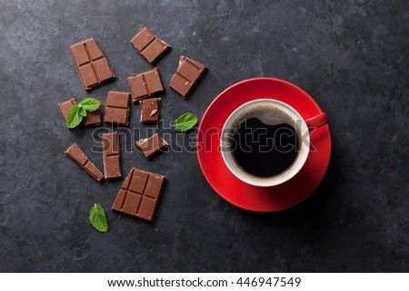 Chocolate and coffee cup on dark stone background. Top view